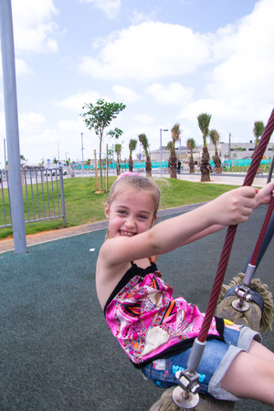 Beautiful girl play outdoor on swing photo