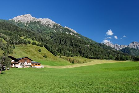 Rural landscape in Austrian Alps: green meadows under mountains Stock Photo