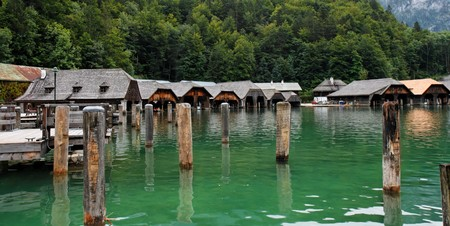 wood pillars: Wooden boat houses and mooring posts on Koenigssee in Bavaria, Germany Stock Photo