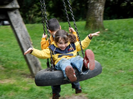 Little girl and boy swing on a hanging tire