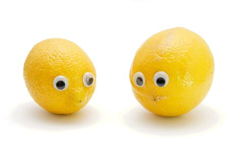 Two funny lemon fruits with eyes on white background