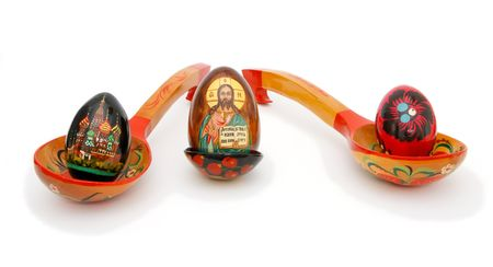 Three Easter eggs in Russian wooden hand-painted spoons on white background photo