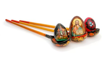 Three Easter eggs in Russian wooden hand-painted spoons with long handles on white background photo