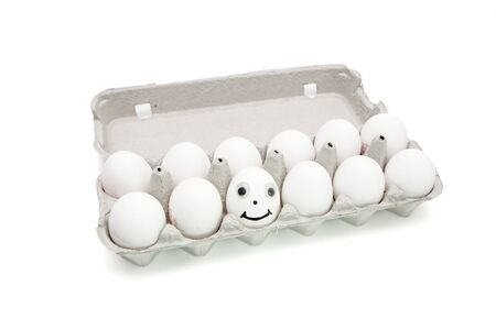 Funny egg with eyes among dozen in a paper box on white background