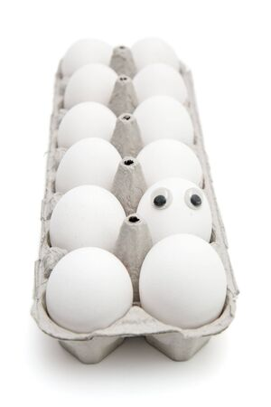 Funny egg with eyes among dozen in a paper box on white background Stock Photo - 4729626