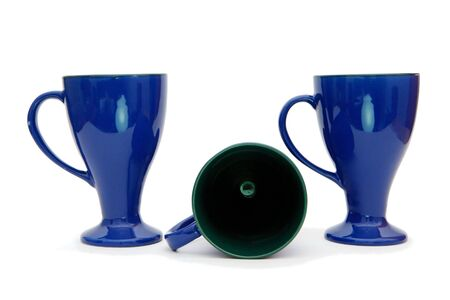 Two standing and one lying blue long-stemmed coffee cups isolated photo