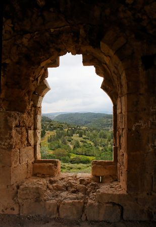 Green hills landscape seen through window of ruined ancient castle