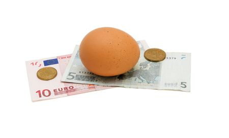 five cents: Brown egg on small euro banknotes with coins isolated