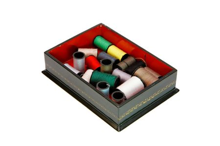 Dark green wooden casket with colorful threads isolated photo