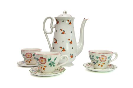 dogroses: White tea service of high teapot and cups with saucers painted with dogroses isolated