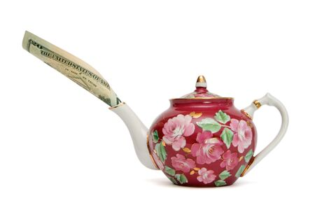 Floral-painted teapot with dollar bill sticking out of its spout isolated  photo