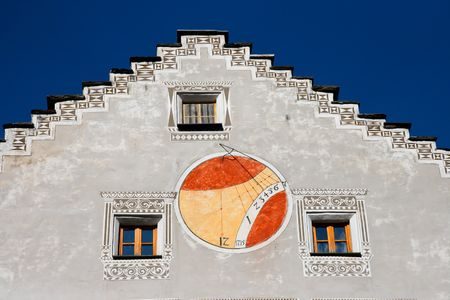 Red and orange sundial on wall of european house photo