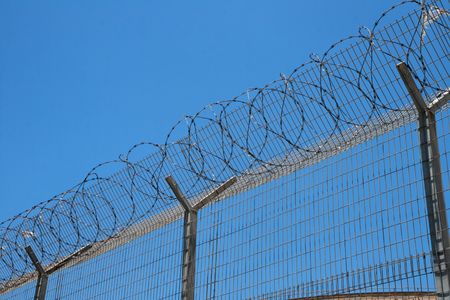 Fence with spiral barbed wire on top on sky background photo