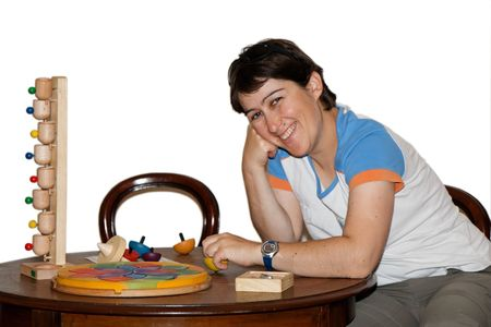 Smiling mid age woman plays with wooden toys isolated photo