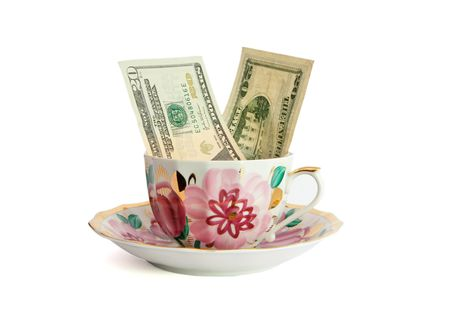 Tea cup with twenty dollar bills sticking out isolated