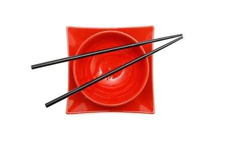 Black chopsticks on red Japanese bowl  and square plate top view isolated photo