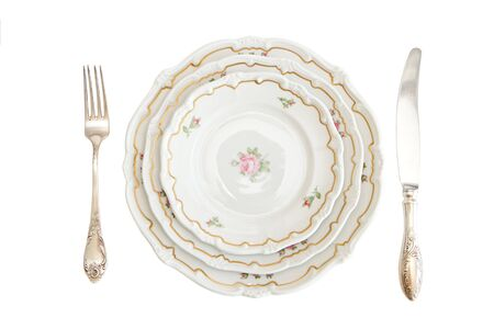 Dinner set with three plates, knife and fork isolated