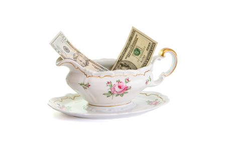 Vintage porcelain sauce-boat with dollar bills isolated  photo
