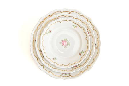 Stack of three white dinner plates and saucers with flowers and wavy rim top view isolated photo
