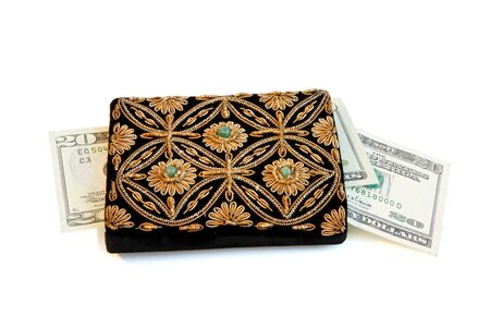 Embroidered womans purse and dollar banknotes isolated photo