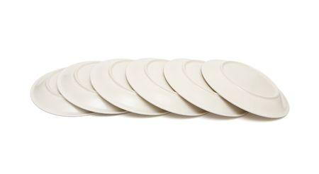 overturned overturn: Stack of plain beige plates tiled upside down isolated Stock Photo