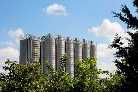 Twelve high metal tower silos on chemical plant behind the trees Stock Photo - 5629039
