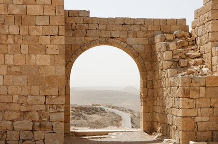 archway: Ancient stone arch and wall with desert view during sandstorm