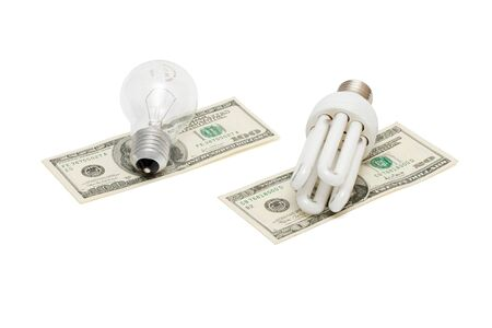Energy save lamp versus bulb on dollar bills isolated photo