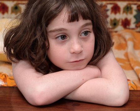 short cut: Serious cute little girl rests her head on crossed arms close-up