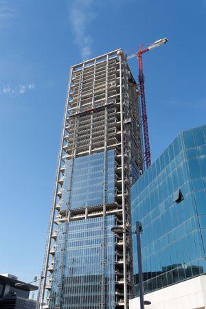 Lifting crane at skyscraper construction site photo