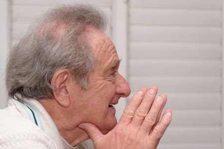 Smiling elderly man resting his head on hands profile closeup Stock Photo