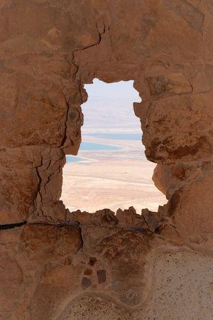 Dead Sea landscape seen through window of ruined Masada fortress photo