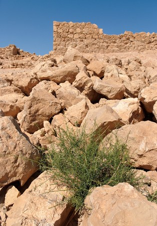Ruins of ancient tower on the rocky hill in Masada fortress in Israel photo