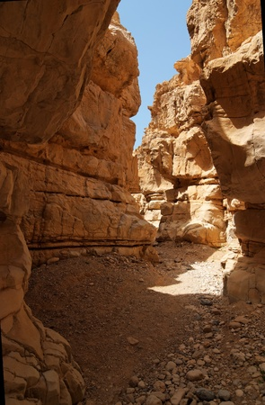 Narrow slot between two rocks in desert canyon photo