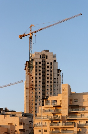 Lifting crane and building under construction at sunset Stock Photo