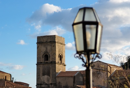 Medieval church and street lantern in Savoca village in Sicily, Italy, at sunset photo