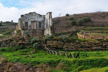 Farmhouse ruin among rural landscape photo