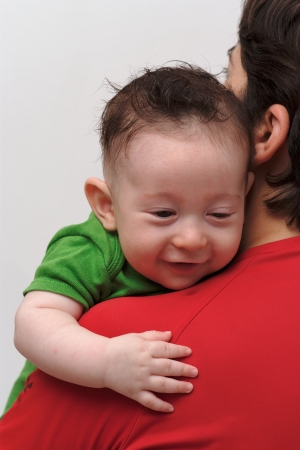 Rear view of cute smiling baby boy  looking over mother  shoulder photo