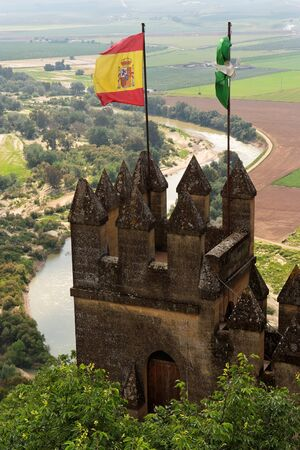 crenelation: Almodovar Del Rio medieval castle with flags of Spain and Andalusia Editorial