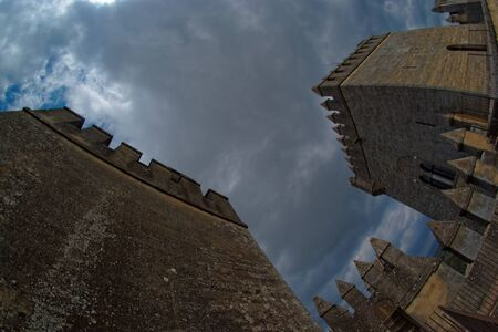 crenelation: Fisheye view of towers of Almodovar del Rio medieval castle against the cloudy sky Editorial