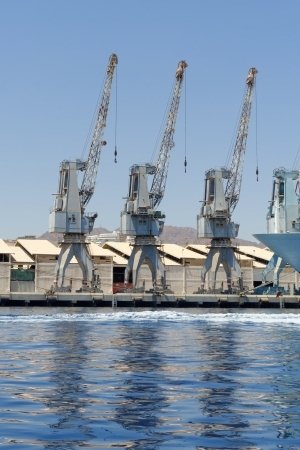 shipload: Row of cranes and their reflections in the sea in Eilat harbor, Israel Stock Photo