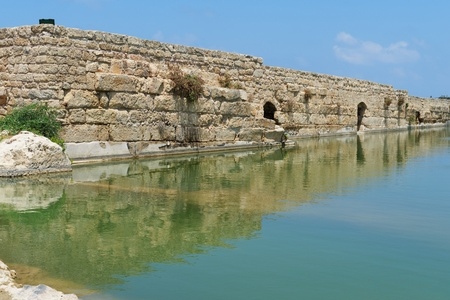nahal: Ancient wall reflecting in the pond in Nahal Taninim archeological park in Israel