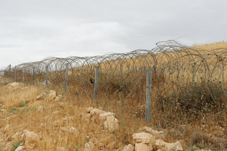 Barbed tape or razor wire fence across the desert hill on cloudy day photo