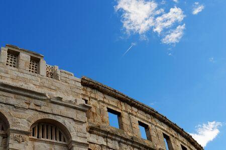 contrail: Contrail of the jet plane above ancient Roman amphitheater in Pula, Croatia