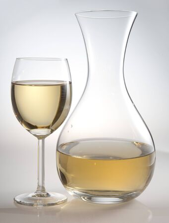 decanter: there are glass and a carafe of white wine on a white background   Stock Photo