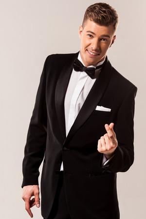 snaps: stylish man snaps his fingers in black tuxedo Stock Photo