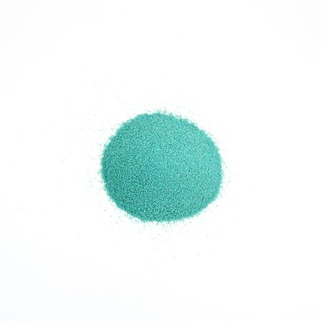 Small round handful of mint coloured sand. Top view on isolated white background.