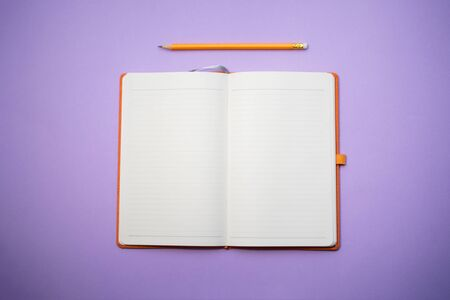 Opened book and pencil on it on the purple background. Space for text. Top on view. Stock Photo