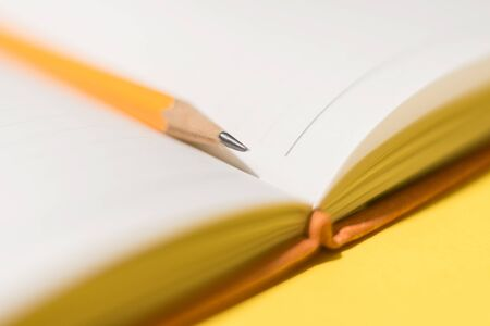 A pencil between pages of the daybook on the yellow background. Concept photo. Stock Photo - 138192918