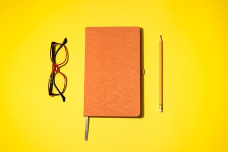 A pencil, orange daybook and red-black glasses on the yellow background. Concept idea. Space for text. Top on view.